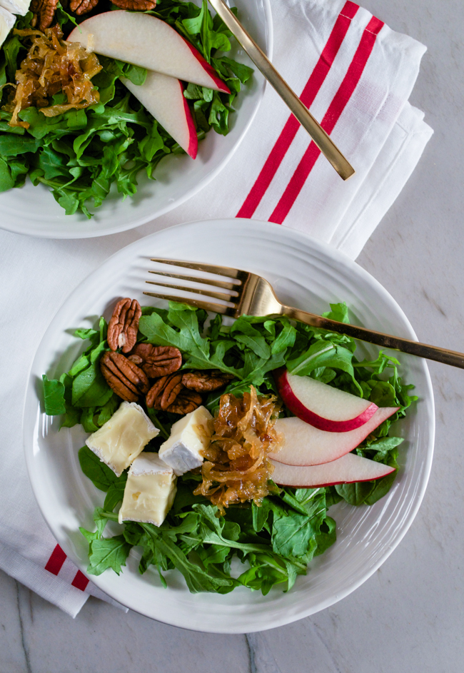 A healthy but decadent salad - Arugula, Pear, Brie, Pecans and Caramelized Onions topped with a sweet Shallot Mustard Vinaigrette from www.sprinkledsideup.com